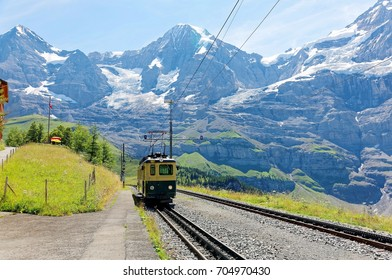 A cog wheel train traveling on the mountain Railway from Wengen to Kleine Scheidegg station with majestic Swiss Alps ( Eiger, Monch, Jungfrau ) in background, in Bernese Highlands, Switzerland, Europe