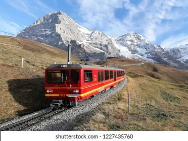 A cog wheel train travels on Jungfrau Railway from Jungfraujoch ( top of Europe) to Kleine Scheidegg on a grassy hillside with a snow shed tunnel under Eiger & Monch, in Bernese Oberland, Switzerland