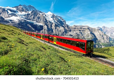 A cog wheel train travels on famous Jungfrau Railway from Kleine Scheidegg on a green grassy hillside to Jungfraujoch station ( top of Europe) on a sunny summer day, in Bernese Oberland, Switzerland