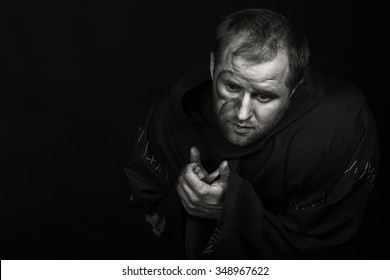 Cogent game actor faithful image of the hero on a dark background. Theater actor in the guise of a beggar. Professional theatrical makeup and costume. Game touching actor.