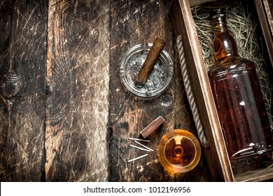 Cognac background. A bottle of cognac in a box with a glass and a cigar. On a wooden background.