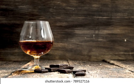 Cognac with bitter chocolate. On a wooden background.
