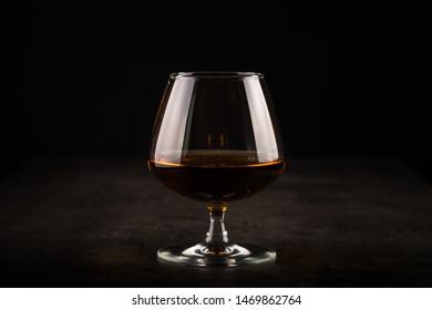 Cognac or brandy in the glass. Dark background.