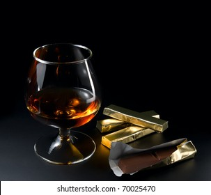 Cognac and chocolate on a black background.
