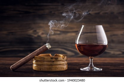 Cognac and cigar. Glass of cognac or brandy with cigars from Cuba Havana and ashtray on natural wooden background. Glass of whiskey with smoke cigar. Alcohol drink on Bar counter in the restaurant.