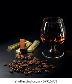 Cognac and coffee beans and chocolate on a black background.