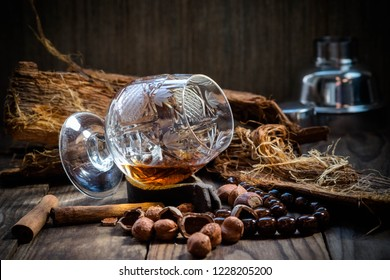 Cognac in a crystal glass on a dark wooden background ...