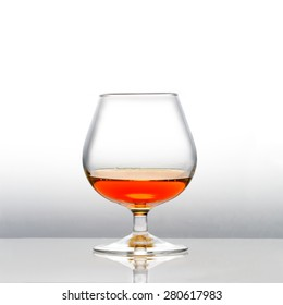 A with cognac filled snifter with slightly reflection of the glass from POV
