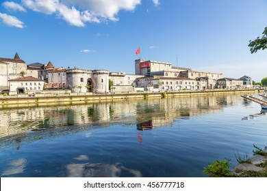 COGNAC, FRANCE - JUL 22, 2015: Quay of the Charente river. From left to right: Valois Castle (X - XV centuries) now Otard cognac house, gates and towers of St. James (1499), the cognac house Hennessy