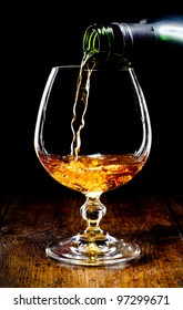 Cognac glass and bottle on a black