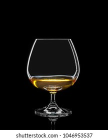 Cognac glass with drink on black background
