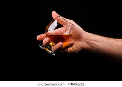 Cognac glass in a hand of a man