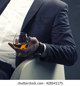 Cognac glass in a hand of a man dressed in suit and white shirt. Toned