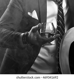 Cognac glass in a hand of a man dressed in suit and tie. Black and white.
