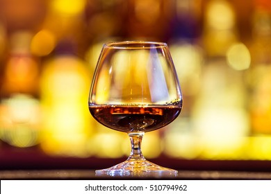 Cognac in a glass on a background of bright lights. Traditional French drink.