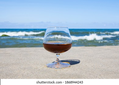 Cognac glass on the background of the sea horizon. Whiskey in a glass on the beach, alcohol and relaxation