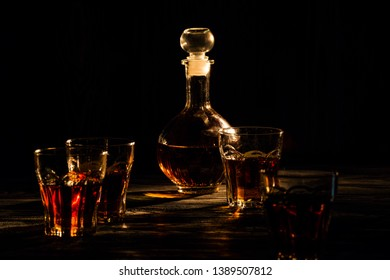 cognac in glasses and decanter, an exquisite alcoholic drink for men, shot in a dark light key