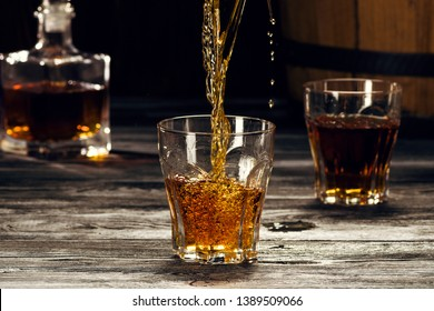 Cognac in glasses, in a wooden barrel cellar, strong refined alcoholic beverage