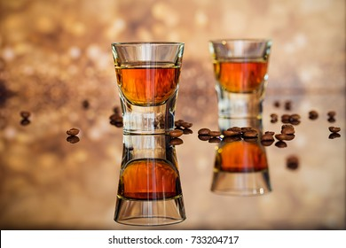 Cognac or liqueur and coffee beans on a glass table. Seasonal holidays concept.