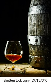 Cognac snifter with glowing golden cognac standing on old flagstones or tiles alongside an old oak barrel in a dark cellar, conceptual of aged matured cognac with copyspace