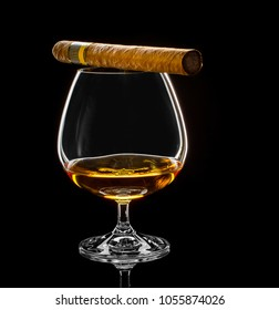 Cognac swivel with golden alcohol and cigar on black background