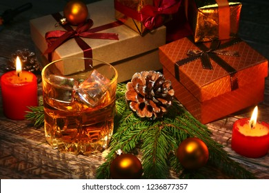 Cognac or whiskey in glass. Christmas balls, gift boxes and candles. New Year's tree, balls and glass with alcohol.