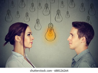 Cognitive skills ability concept, male vs female. Man and woman looking at bright light bulb isolated on gray wall background