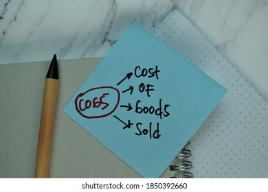 COGS - Cost Of Goods Sold write on sticky note isolated on Wooden Table. Selective focus on COGS - Cost Of Goods Sold text