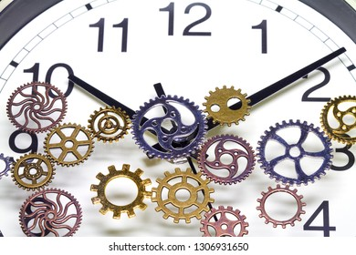 Cogs lie on the dial of a clock.