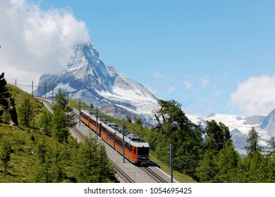A cogwheel train travels on Gornergrat railway through a forest by the mountainside with majestic Matterhorn mountain peak in background on a cloudy sunny summer day, in Zermatt, Valais, Switzerland
