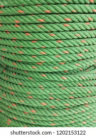 The coil of 6 mm. green nylon rope alternating orange color. Nylon is the strongest of all ropes in common use,such as  lifting or towing heavy load.