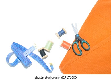 Coil with thread, scissors and ruler on a piece with a bright cloth, on a white background. mock up