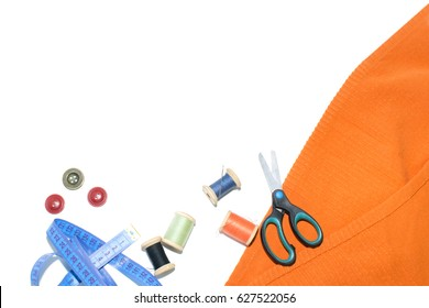 Coil with thread, scissors and ruler on a piece with a bright cloth, on a white background.
