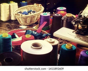 Coil threads for overlock and measuring tape in sewing supplies in on morning sunrise light sun flare. Sewing accessories helps to make our clothes fashionable.