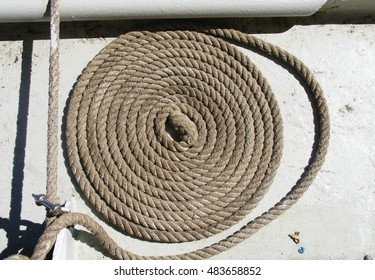 Coil of twisted braided rope attached to metal bar