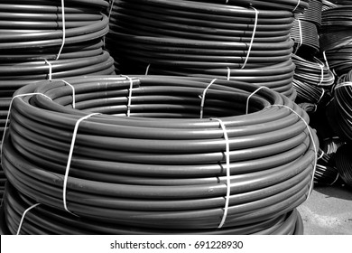 Coiled black plastic pipes stored outdoors