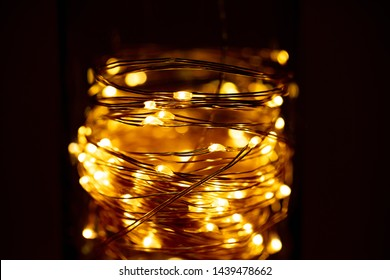 Coiled LED lights lit up in a glass jar. mason jar lights abstract.