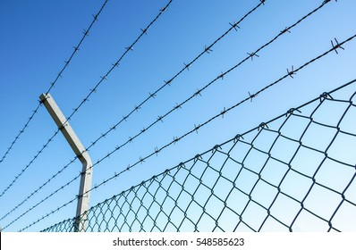 Coiled razor wire with its sharp steel barbs on top of a mesh perimeter fence ensuring safety and security, preventing access or the escape prisoners, blue sky background