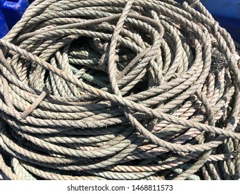 Coiled rope. Weathered grey natural sisal roped string bundle. Fishing equipment. No people. Object.
