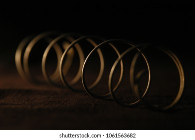 Coiled wire on black cloth lit by one light on the side. Silver wire coil on black background. Single coil wire on black cloth, sepia toned shallow DOF.