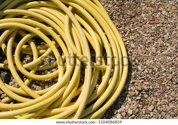 Coiled yellow hosepipe on a gravel background