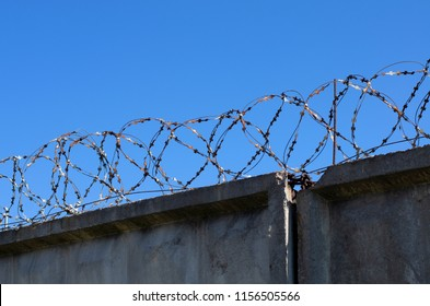 Coils of barbed wire with spikes over the concrete fence in the background blue sky
