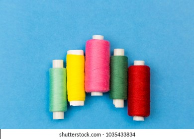 Coils with multi-colored threads on a blue background. Threads for sewing different colors are arranged in steps on a blue background.