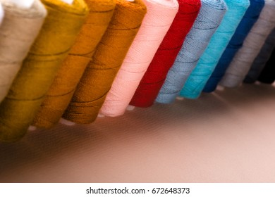 Coils with multi-colored threads on a pink background.