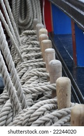 Coils of rope slung around a row of wooden pegs