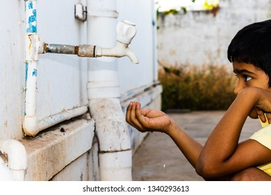 Coimbatore, Tamilnadu,INDIA- MARCH 2019.  A boy looking at a tap, holding water droplets