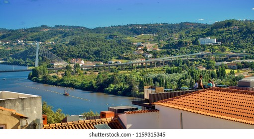 Coimbra, August 8th 2018 : Rainha Santa Isabel bridge crossing the Mondego River with view of rooftops and the green mountains of Santa Clara