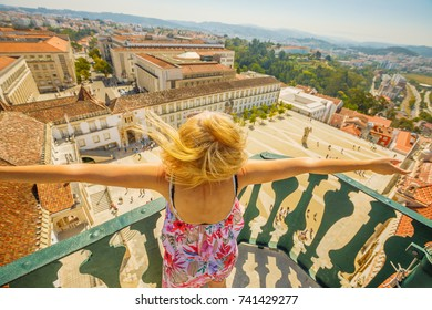 Coimbra city skyline and University courtyard. Happy tourist woman with open arms admiring Coimbra panorama from top of bell Clock Tower. Female tourist enjoys in Portugal, Europe.
