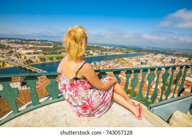 Coimbra cityscape and Santa Clara Bridge on Mondego river. Caucasian tourist woman admiring Coimbra panorama sitting on top of bell Clock Tower. Female tourist enjoys in Portugal, Europe.
