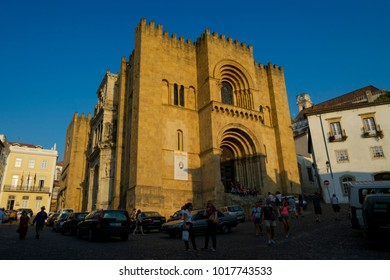COIMBRA, PORTUGAL - August 13, 2016: Tourists outside the western facade of the Old Cathedral (Se Velha in Portuguese) in Coimbra, Portugal on August 13, 2016